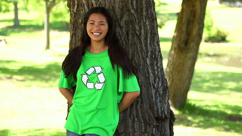 Happy environmental activist leaning against a tree Footage