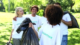 Happy volunteers picking up trash in the park Footage