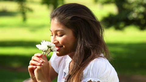 Pretty girl sitting on the grass smelling flowers Footage