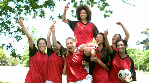 Female football team celebrating a win in the park Footage