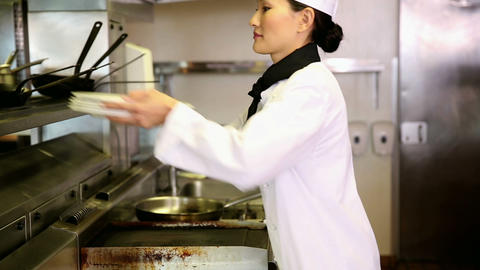 Asian chef putting away stack of plates Footage