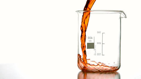 Orange Liquid Pouring Into Beaker stock footage