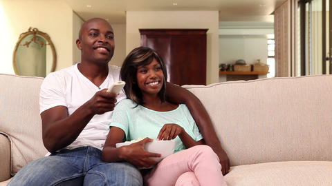 Happy Couple Watching Tv On The Couch stock footage