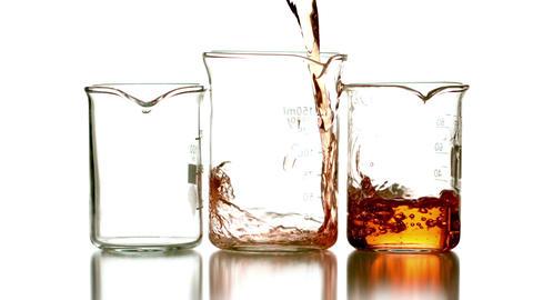 Orange liquid pouring into three beakers Footage