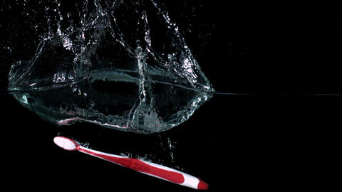 Pink toothbrush falling in water on black background Footage