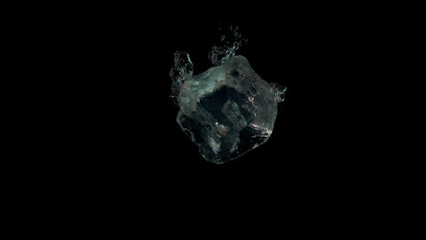 Ice cubes falling in water on black background Footage