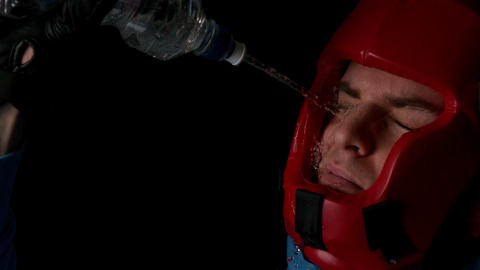 Boxer pouring water from bottle over face Footage