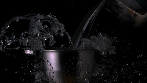 Water pouring over colander on black background Footage