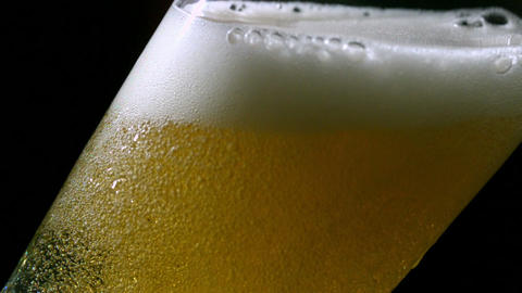 Beer pouring into glass on black background Footage