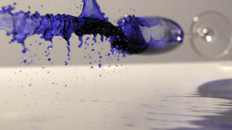 Glass of blue ink falling and spilling Footage