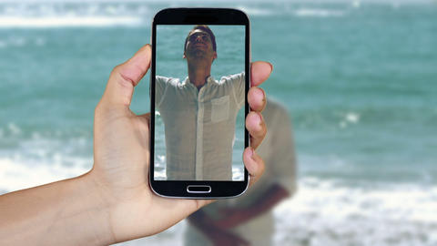 Hand showing beach and holiday clips on smartphone Animation