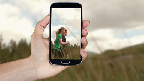 Hand showing running and adventure clips on smartphone Animation
