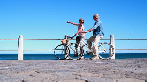 Active Seniors Going On A Bike Ride By The Sea stock footage