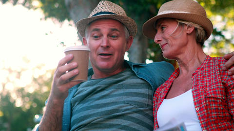 Happy tourist couple sitting on bench holding map Footage