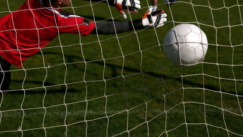 Goalkeeper in red letting in a goal during a game Footage