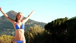 Beautiful blonde enjoying the sunshine in bikini Footage