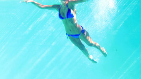 Sexy blonde in blue bikini jumping into the swimming pool Footage