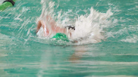 Fit swimmer doing the front stroke in the swimming pool Live Action
