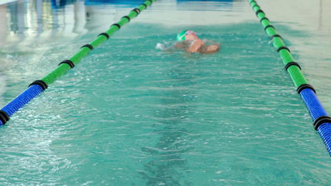 Fit swimmer doing the back stroke in the swimming pool Live Action