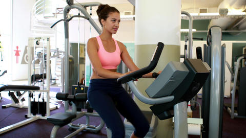 Fit brunette working out on the exercise bike Footage
