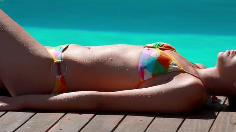Sexy brunette lying poolside sunbathing Footage