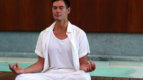 Calm man in white sitting in lotus pose Footage