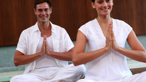 Smiling couple in white sitting in lotus pose with Footage