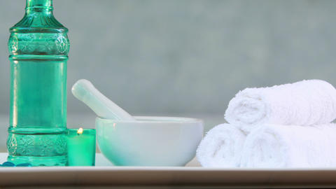 Towels and glass bottle with candle and mortar and pestle Live Action