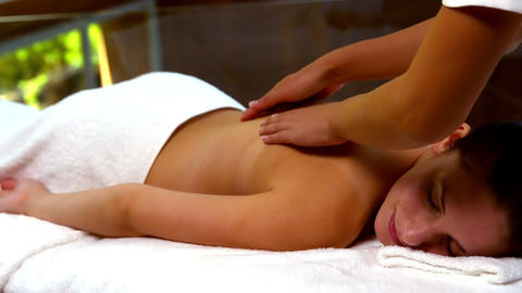Peaceful woman enjoying a back massage at the spa Live Action