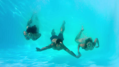 Friends swimming underwater in pool together Live Action