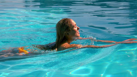 Sexy blonde swimming across the pool Footage