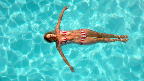 Woman floating in the swimming pool Footage