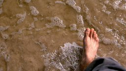 Man walking by the sea barefoot Live Action