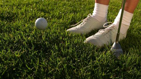 Golf ball falling beside lady golfers feet and clu Footage