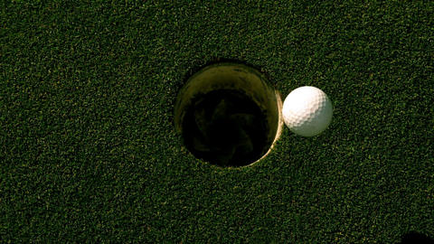 Golf ball rolling into the hole on putting green Footage