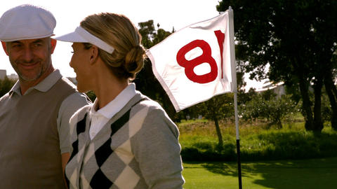 Golfing couple smiling at the eighteenth hole on the golf course Live Action