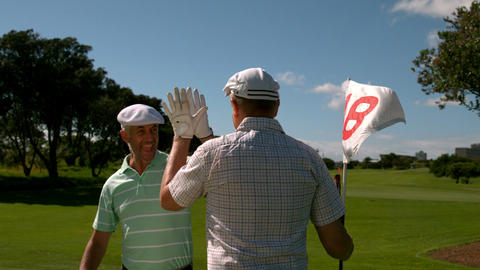 Golfers high fiving on the eighteenth hole Live Action