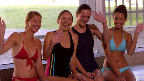 Happy group of women sitting poolside waving at ca Footage