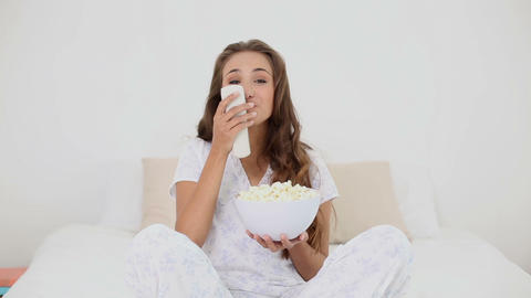 Young woman eating bowl of popcorn on bed and watc Footage