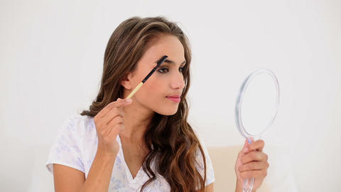 Young woman brushing her eyebrows and looking in h Footage