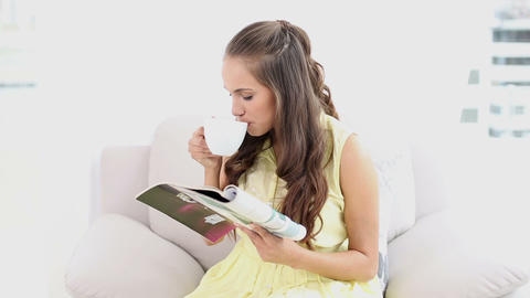 Young woman drinking coffee and reading a magazine Footage