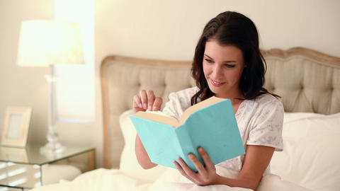 Beautiful brunette sitting in bed reading a book Footage