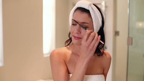 Beautiful brunette wearing a towel doing her eyebr Footage