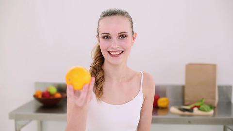 Smiling model smelling an orange Footage