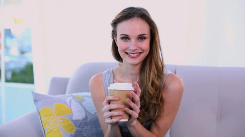 Happy model drinking a coffee on the couch Footage