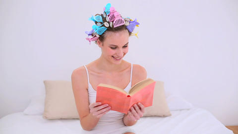 Young model in hair rollers reading a book on her  Footage