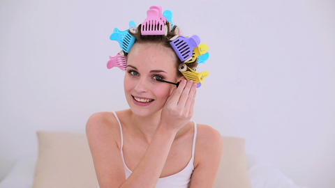 Young model in hair rollers putting on mascara Footage