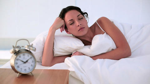 Brunette lying in bed feeling tired in the morning Footage