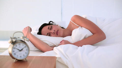 Brunette being woken by her alarm clock in bed Footage