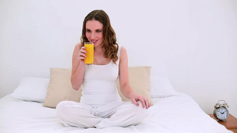 Pretty model sitting on bed drinking glass of oran Footage